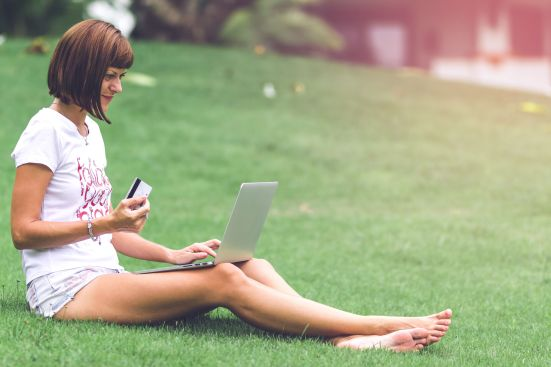Woman online shopping concept. Woman in the green park with mode